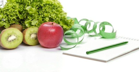 Weight loss program Toronto: pen on notepad measuring tape fruits and vegetables on desk