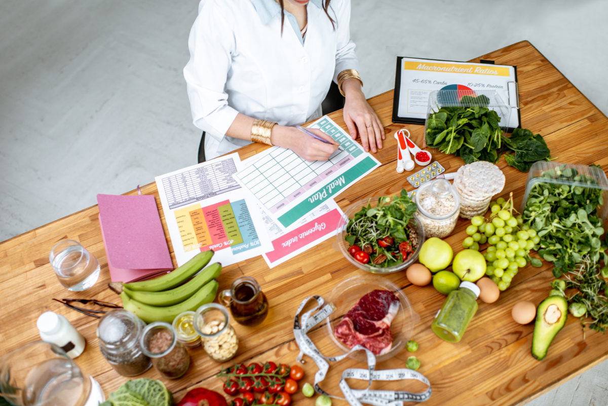 Nutritionist Toronto, Dietitian Toronto creating a meal plan on a table littered with food
