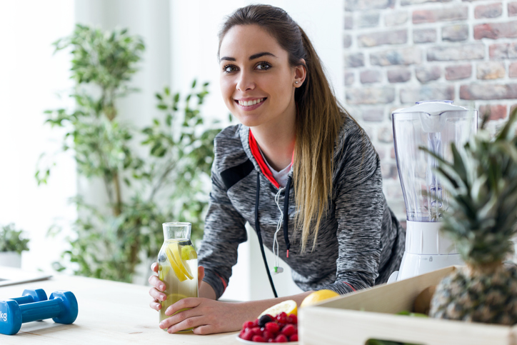 sports nutritionist leaning on counter holding a bottle of water