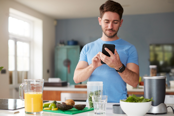 Sports nutritionist Toronto, sports dietitian, exercise physiologist: man at kitchen counter using his phone to count calories & macros