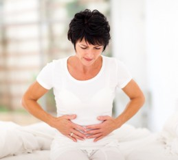 Hard to digest foods, worst foods for digestion: woman holding stomach in digestive pain