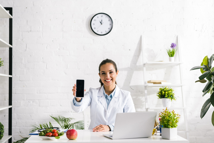 Nutritionist and Dietitian Services: Nutritionist holding phone out while at desk on laptop