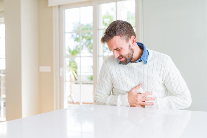 digestive health man holding abdomen in pain