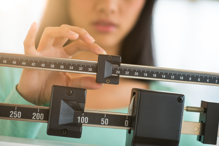 Woman adjusting scale while on a weight loss meal plan