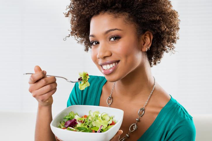 woman enjoying a salad on a women's health meal plan